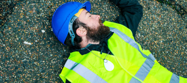 A Lone Worker wearing hi-vis and safety helmet lies on the ground
