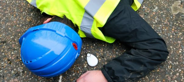 A lone worker in high vis jacket and hard hat lies injured on the ground