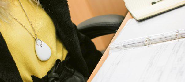 Office worker wearing lone alarm at desk