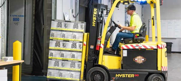 Lone worker moving boxes on forklift